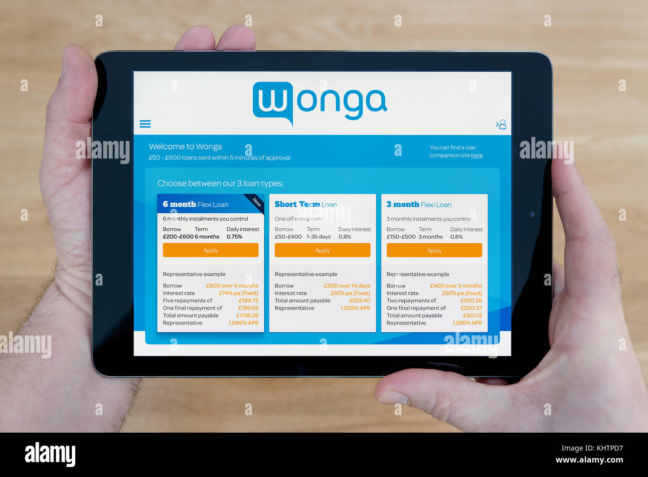 A man looks at the Wonga website on his iPad tablet device, shot against a wooden table top background (Editorial Stock Photo