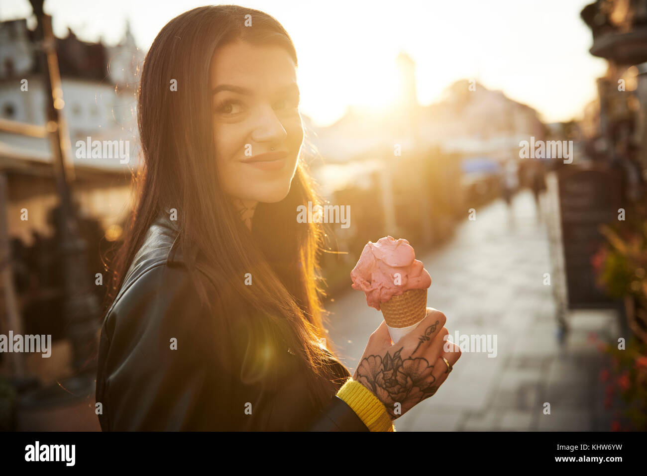Portrait of young woman holding ice cream, tattoos on hand - Stock Image