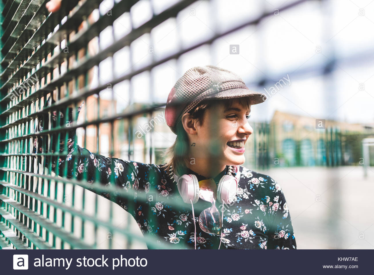 Retro styled young woman in baker boy hat behind wire fence - Stock Image
