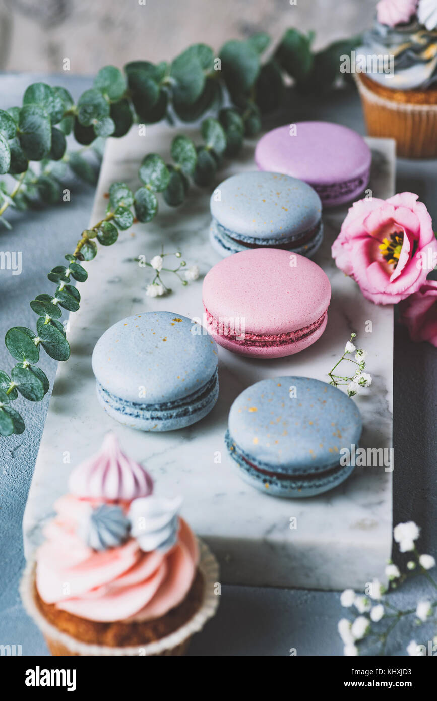 Pastel macarons, cupcakes and flowers on marble background. Wedding sweets, wedding cupcakes and macaroons. Selective - Stock Image