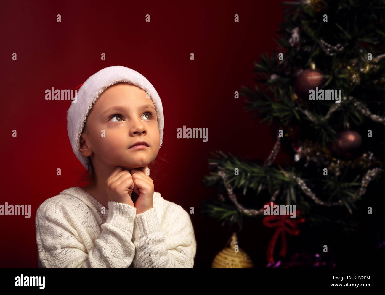 6df9558cf77f9 Cute happy smiling girl in fur santa claus hat near the Christmas holiday  tree asking