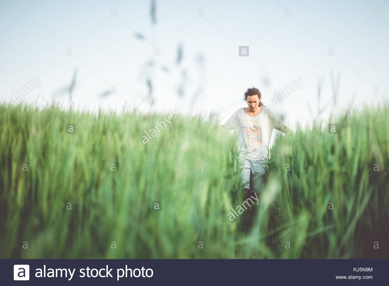 Man walking through green field Stock Photo