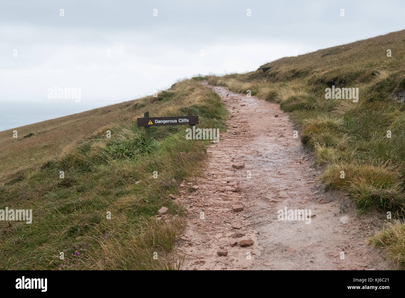 dangerous cliffs sign next to footpath disappearing into the distance, Hoy, Orkney, Scotland, UK - Stock Image