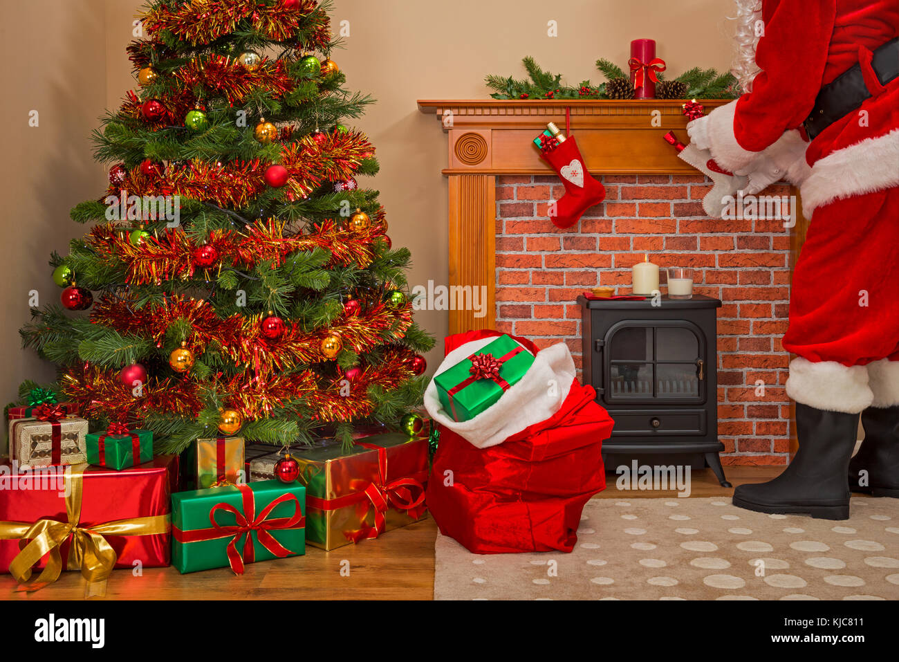 Santa Claus delivering gift wrapped presents under the tree on Christmas Eve with a sack full of toys for good girls - Stock Image