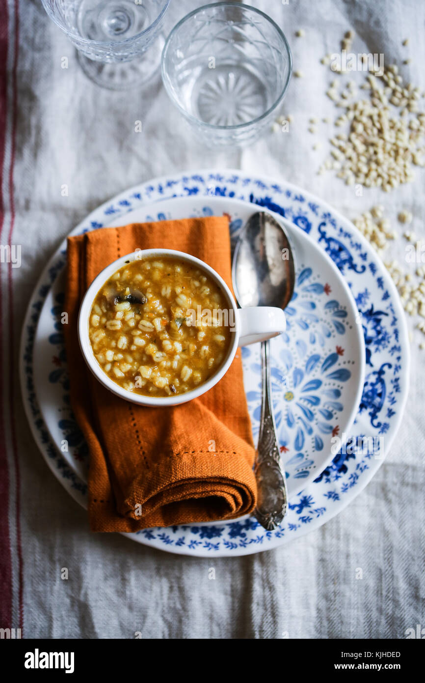 Pumpkin, mushroom and barley soup in a white bowl on a wood table. - Stock Image