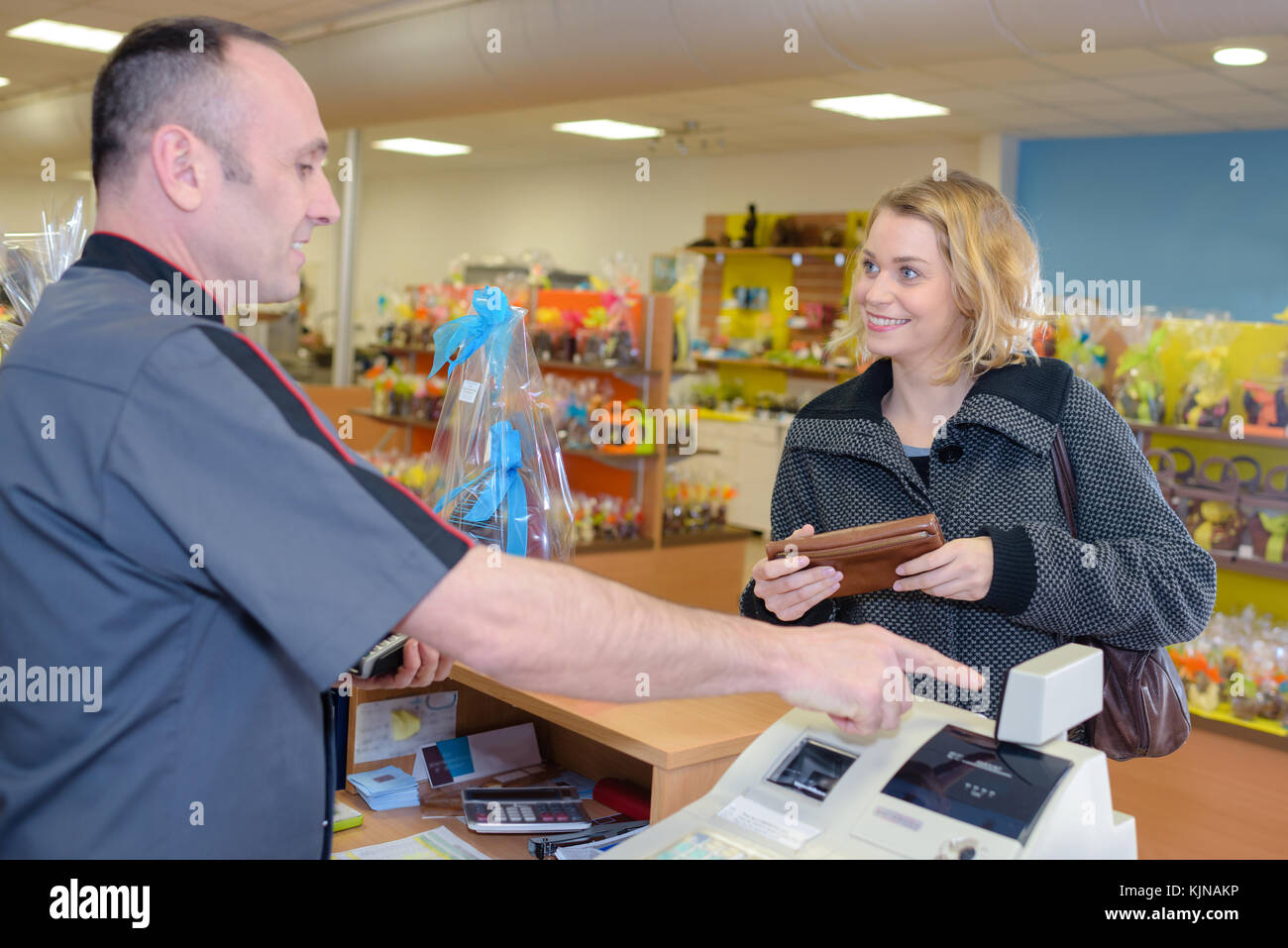 smiling young male store clerk serving purchaser at cash desk - Stock Image
