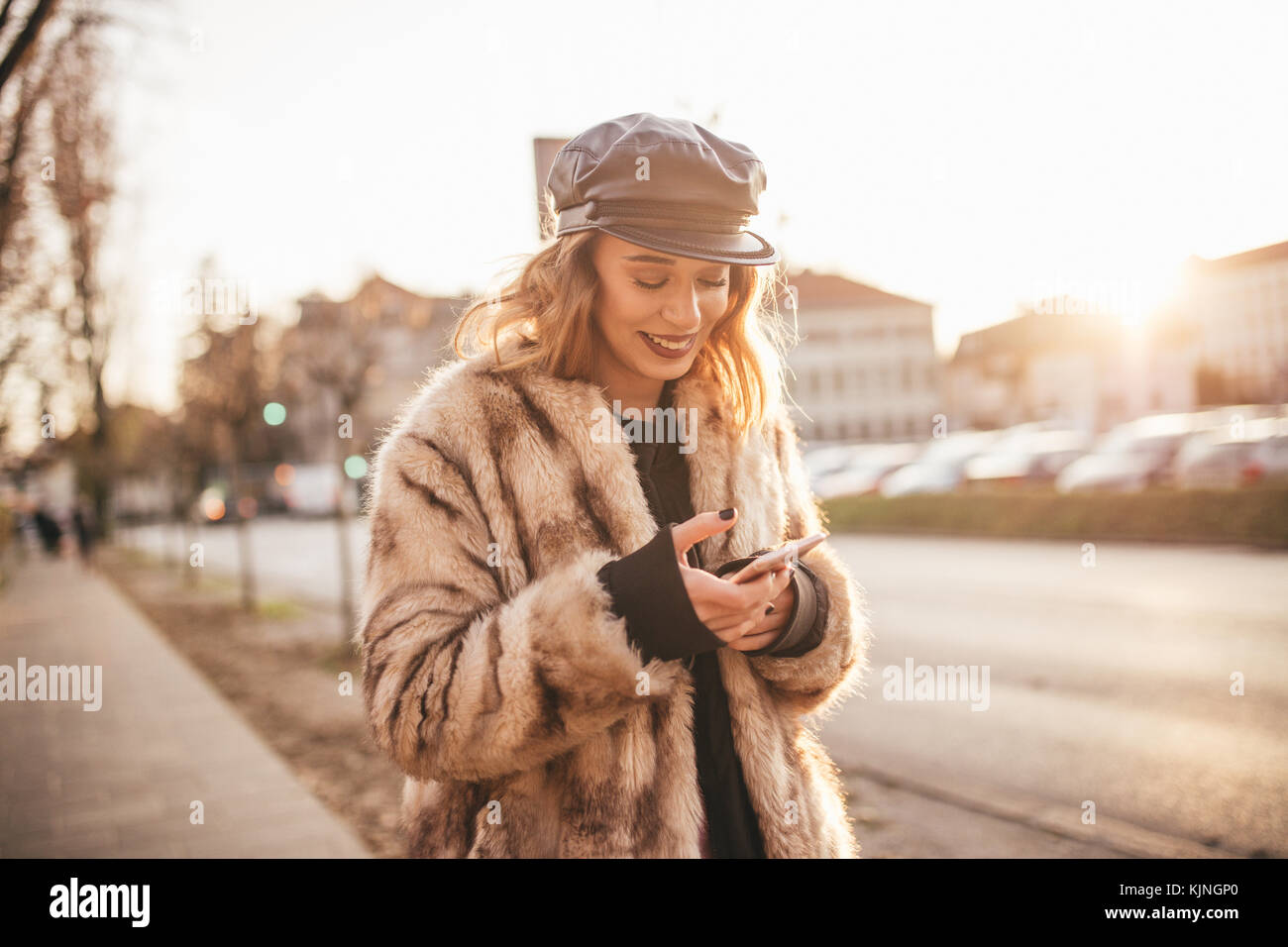 Beautiful girl smiling and texting on her cell phone on city streets - Stock Image