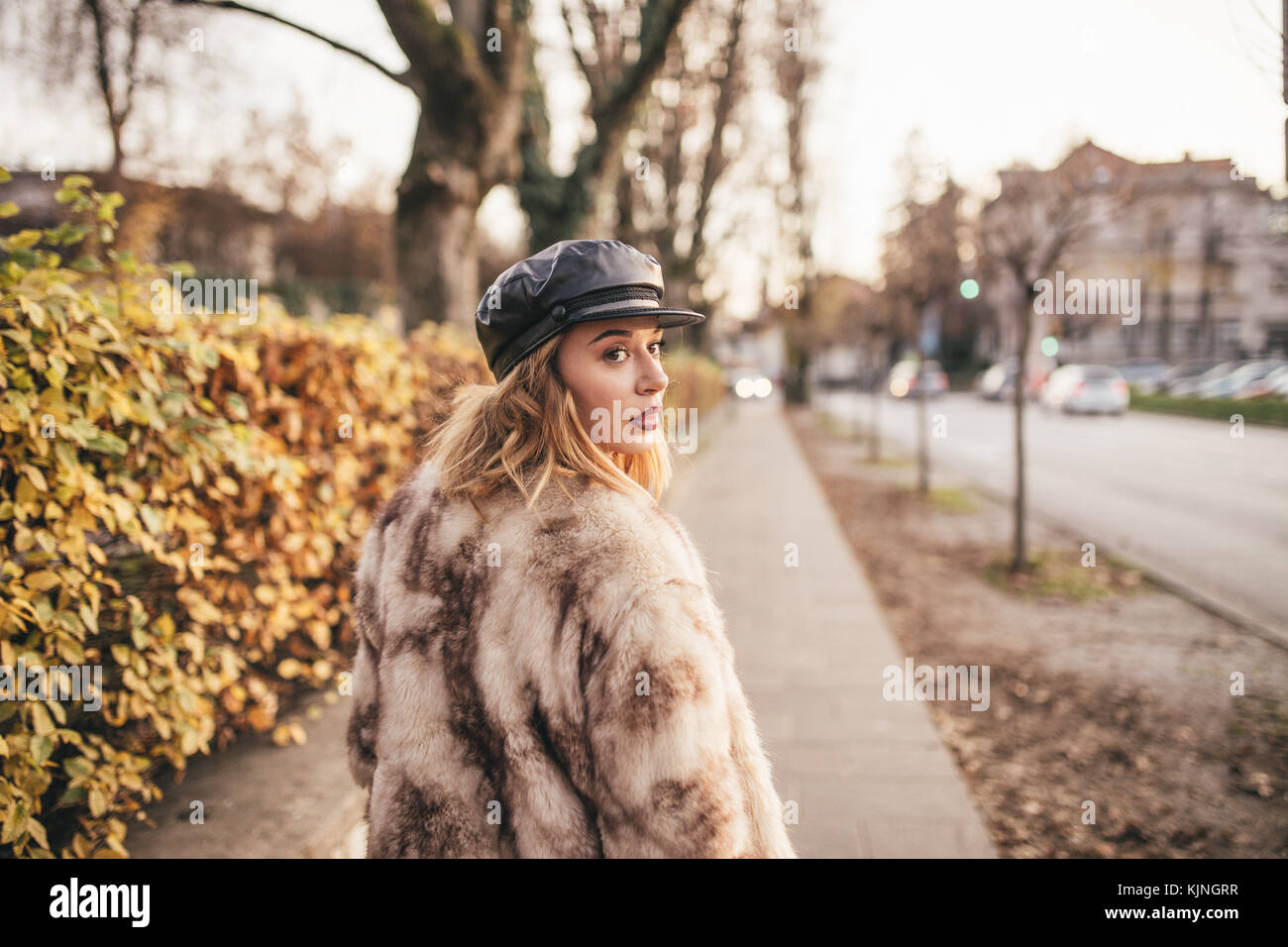 Beautiful girl wearing fur and riding her bike on the city streets - Stock Image