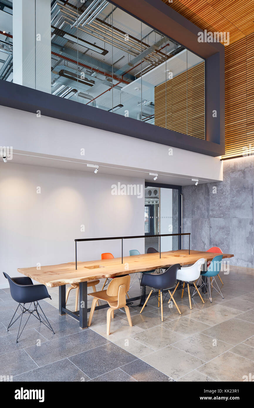 Communal work table in double-height foyer. Thames Tower, Reading, United Kingdom. Architect: dn-a architects, 2017. - Stock Image