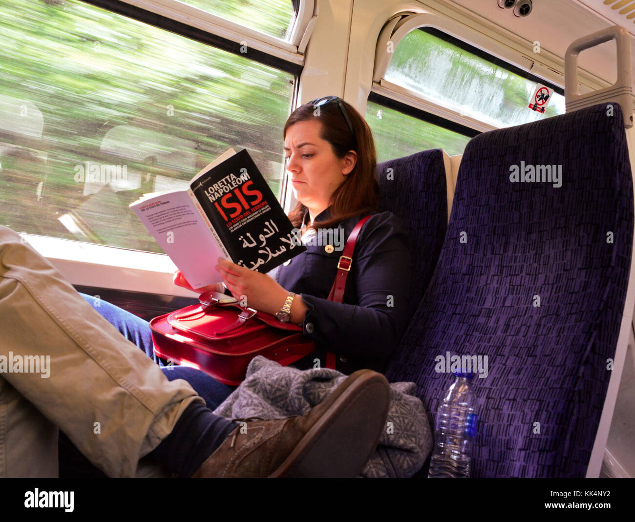 Girl on train reading 'ISIS@ - Stock Image
