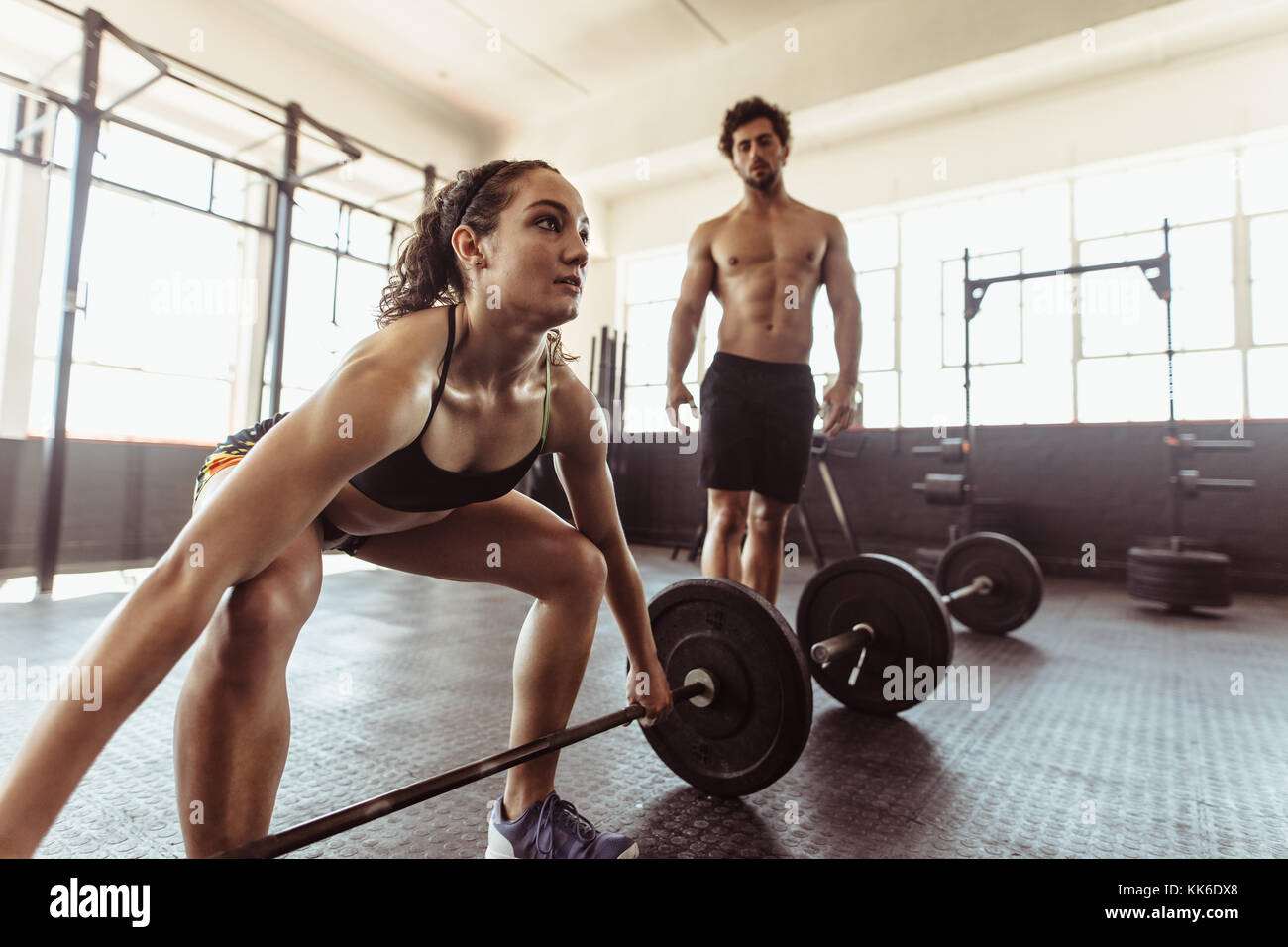 cf6eb2a769a9 Fit young woman exercising with barbell and man standing in background.  Female athlete lifting heavy weights at cross training gym.