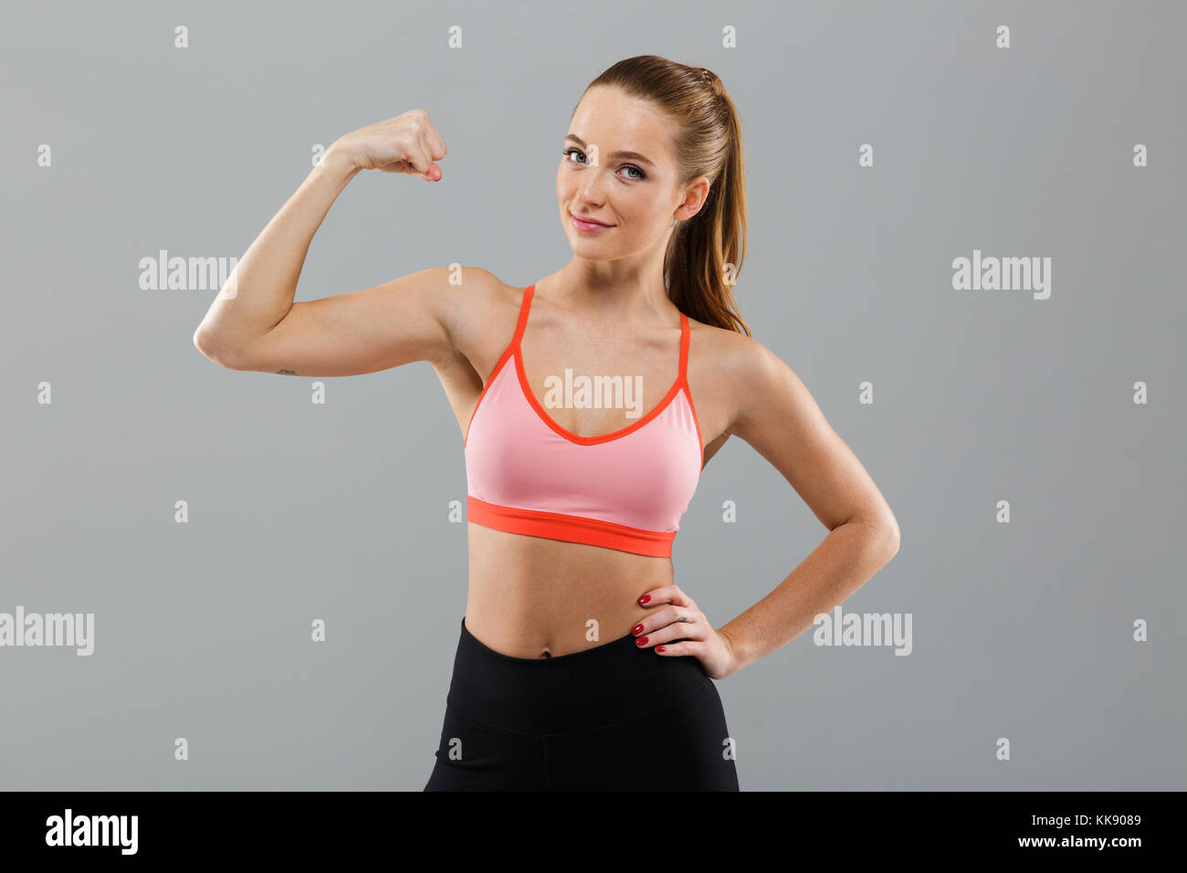 Portrait Of A Smiling Confident Sports Girl Flexing Biceps And Looking At Camera Isolated Over Gray Background