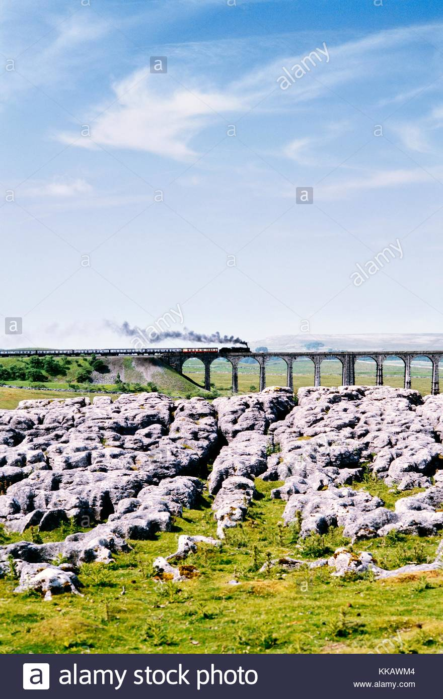 Steam railway engine train crosses the Ribblehead Viaduct in the limestone landscape of Yorkshire Dales National - Stock Image