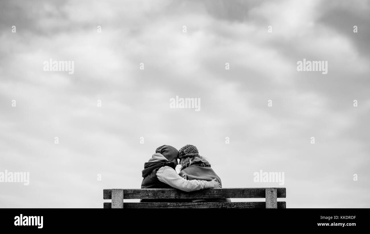 Romantic couple in love sitting on a bench on the Howth`s pier hugging and kissing, Howth Peninsula, Dublin, Ireland Stock Photo