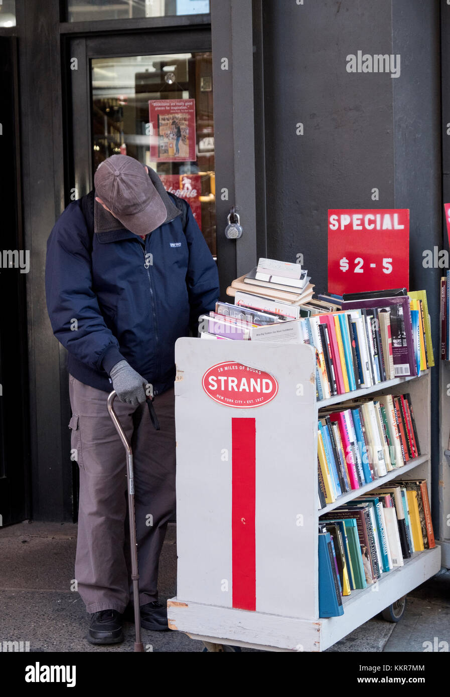 An unidentified senior citizen with a cane browsing the sale book racks outside the Strand bookstore on Broadway - Stock Image