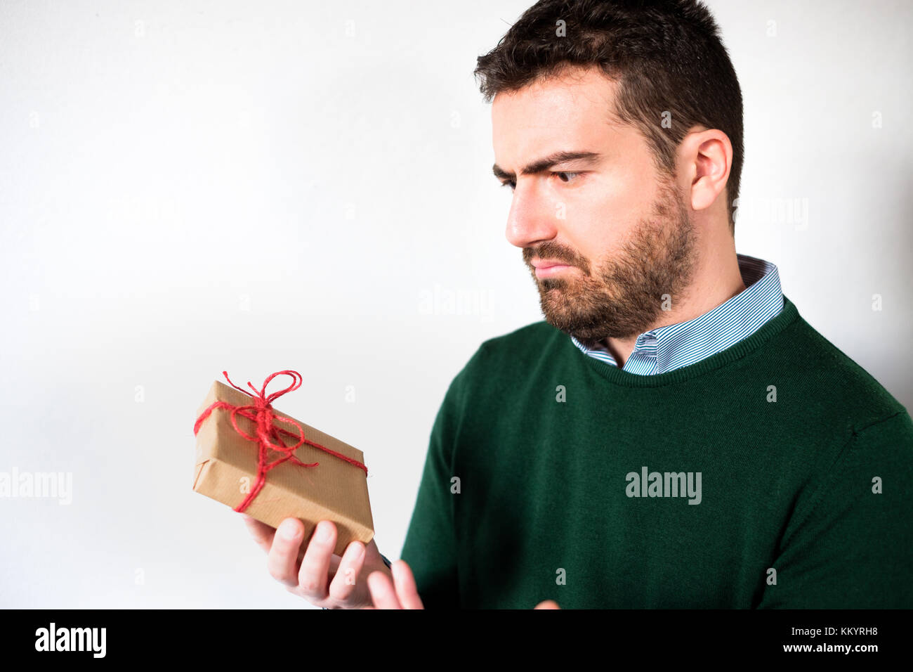 Funny face of a man disappointed by the small gift box , empty copy space for textStock Photo