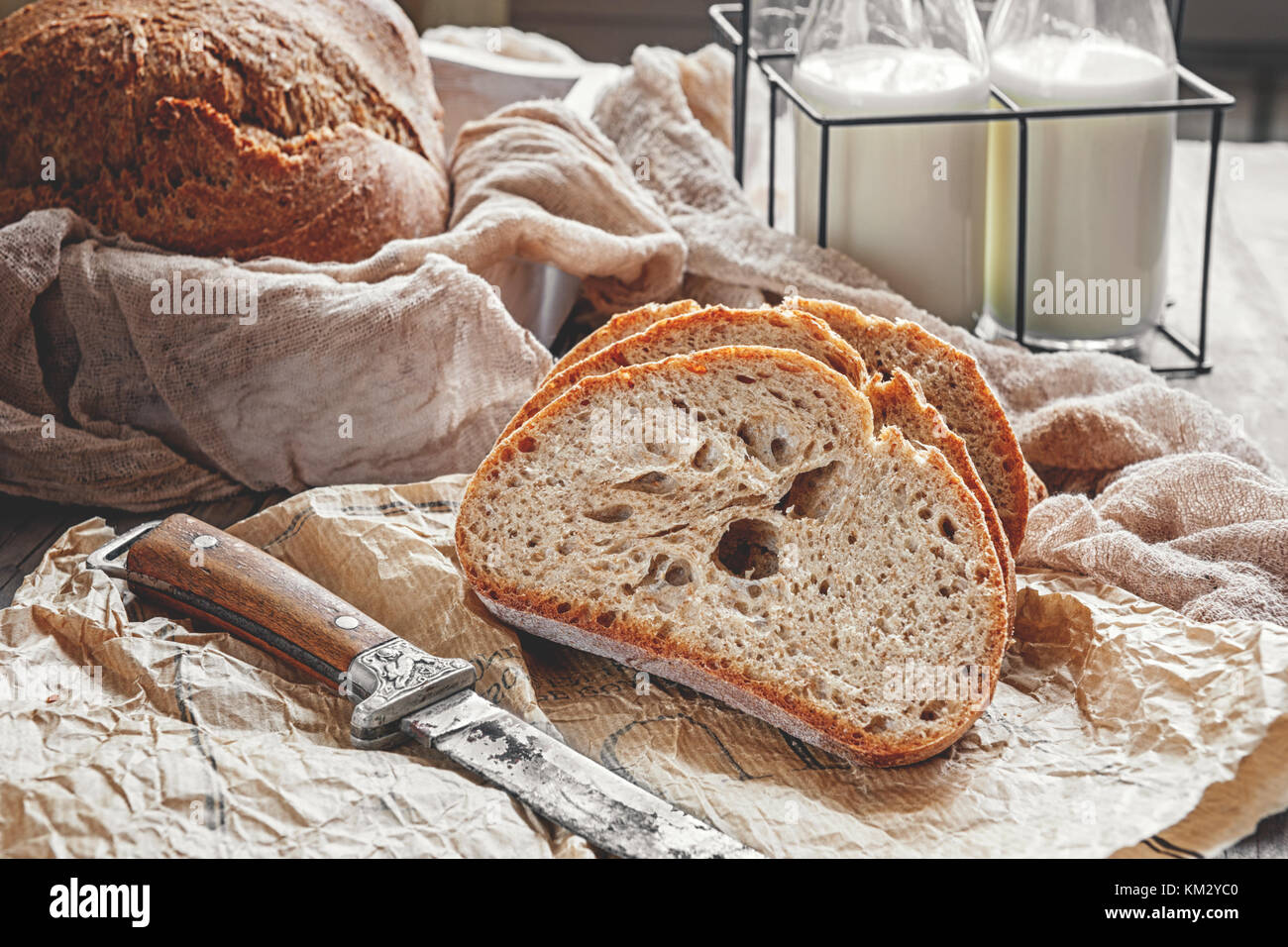 A beautiful loaf of sourdough bread from white wheat on a plate on a linen edge. Homemade pastries. Stock Photo
