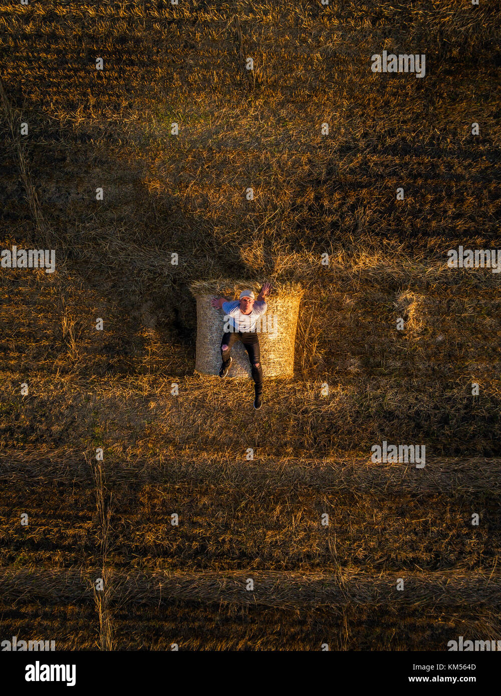 Young man enjoys sunset at the top of a hay bale - Stock Image
