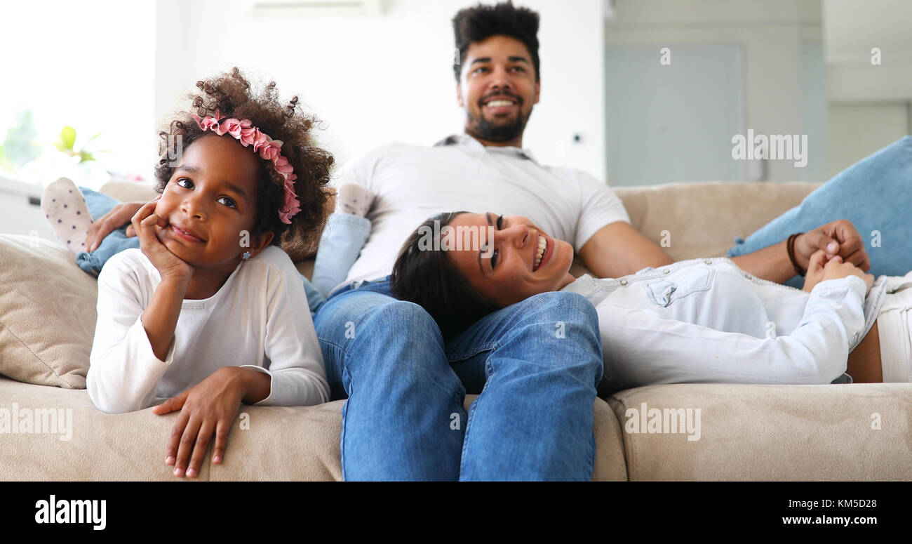 Young girl watching tv with her parents - Stock Image