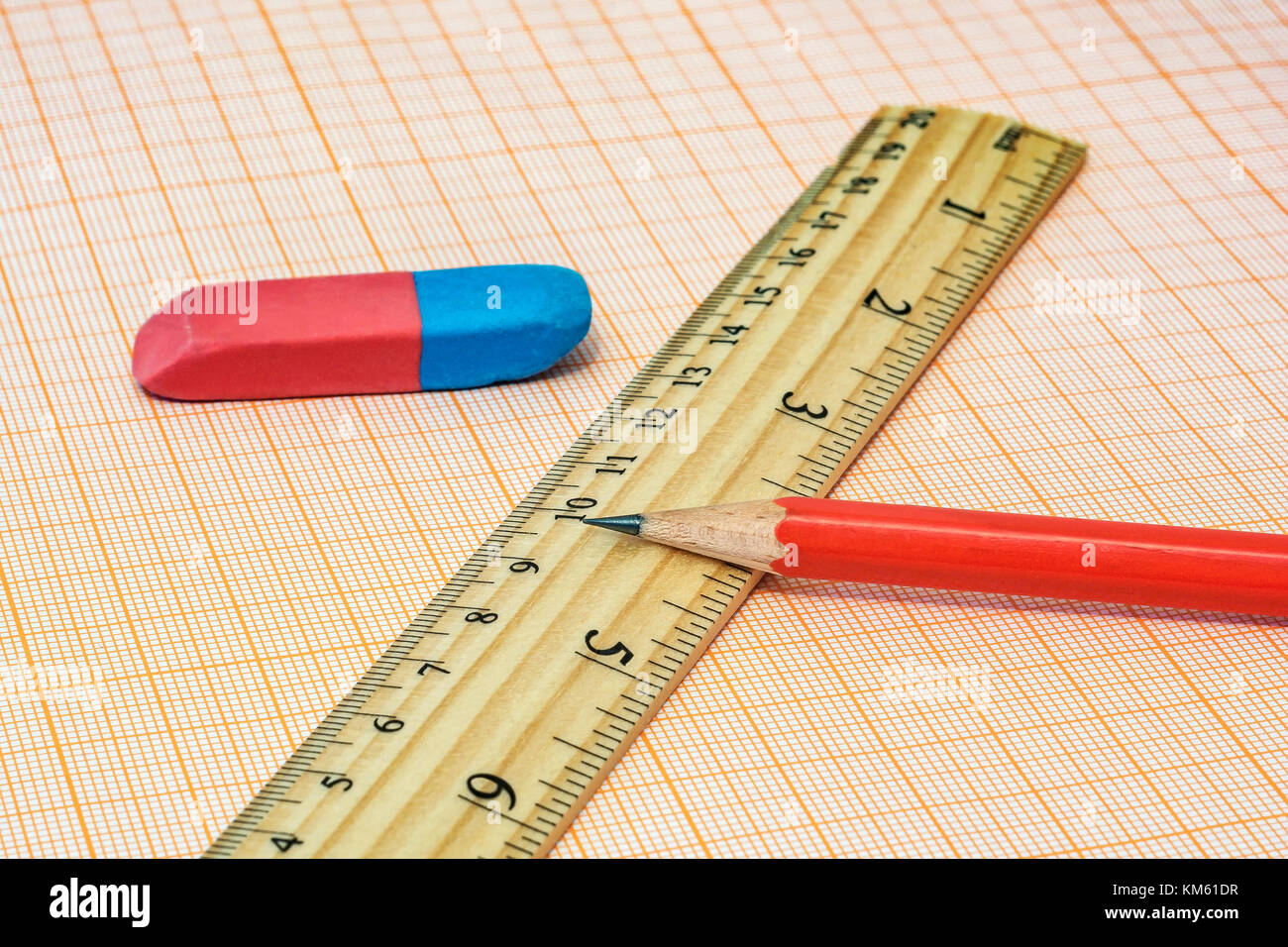 On the millimeter paper lie an eraser with a ruler and a simple pencil close-up - Stock Image