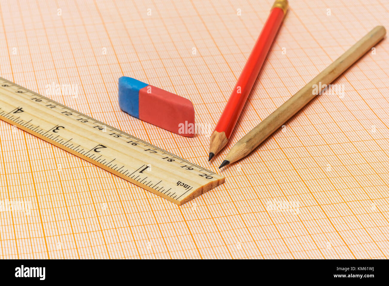 On a millimeter paper there is a wooden ruler, an eraser and two simple pencils - Stock Image