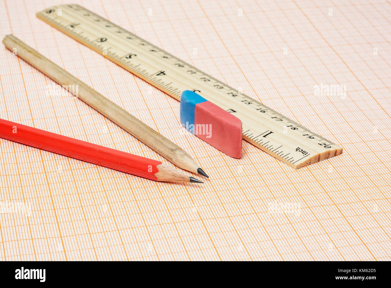 On the millimeter paper there are two simple pencils with an eraser and a ruler - Stock Image