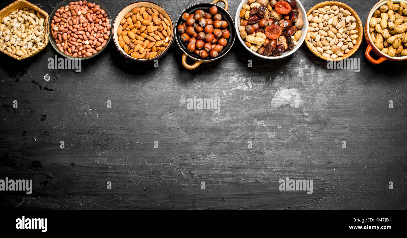 Various nuts in bowls. On a black chalkboard. - Stock Image