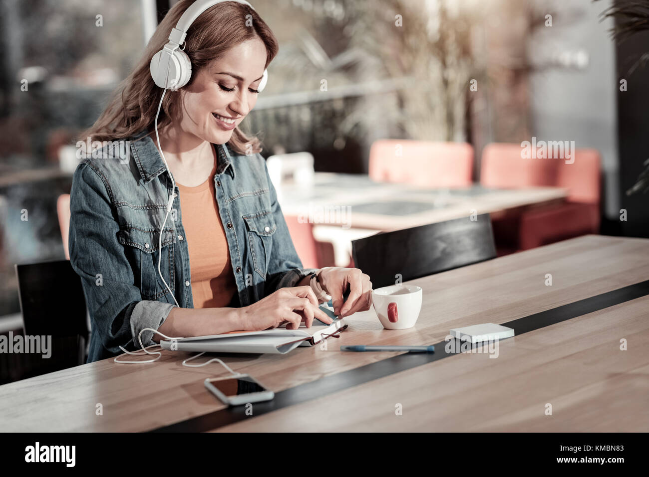 Smiling young woman having a productive morning in a cafe - Stock Image