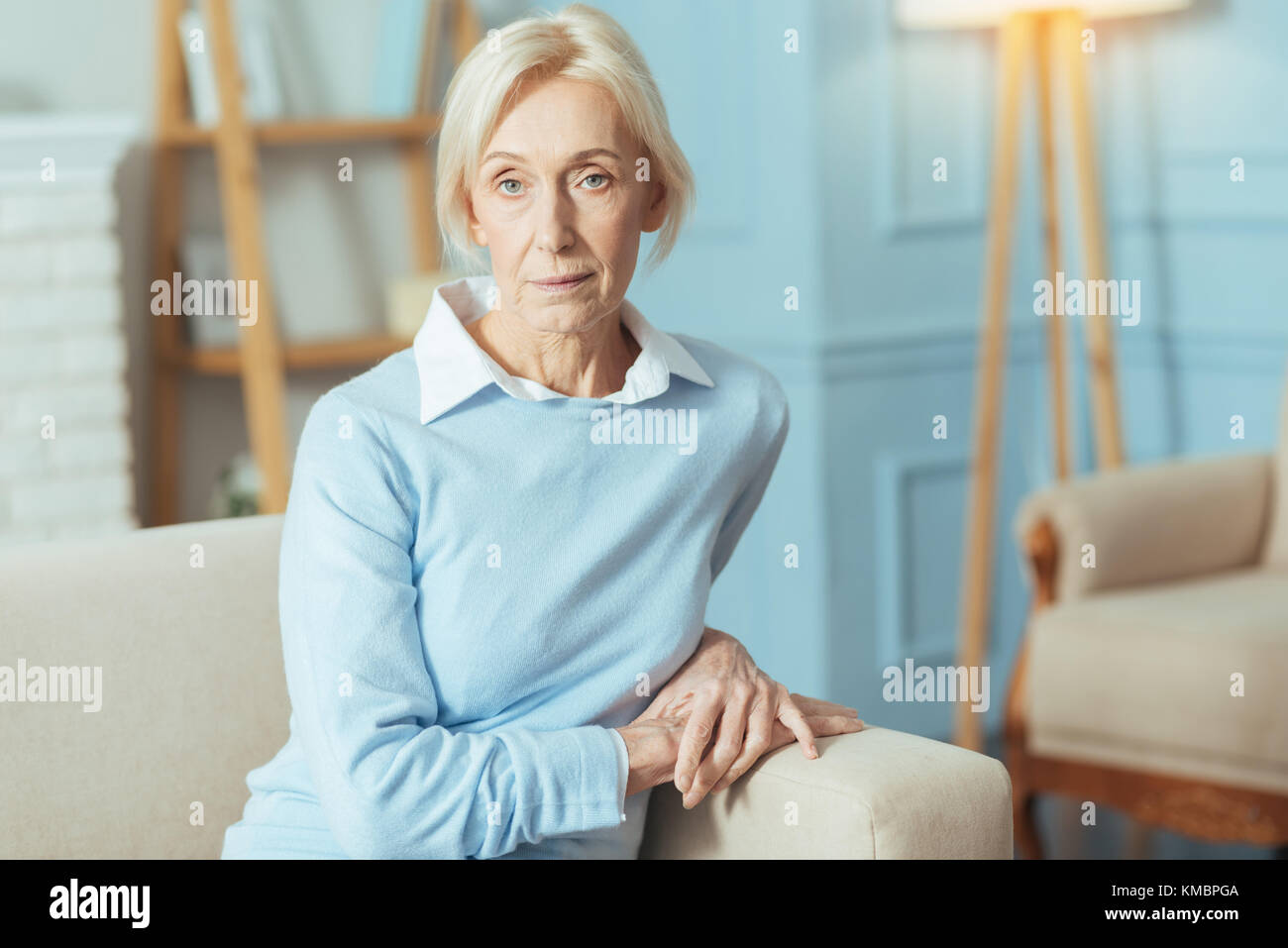 Calm senior woman sitting and waiting for her doctor - Stock Image