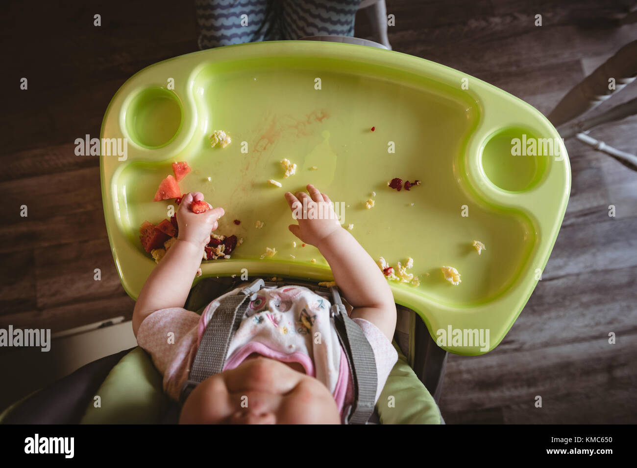 Overhead of baby sitting in high chair - Stock Image