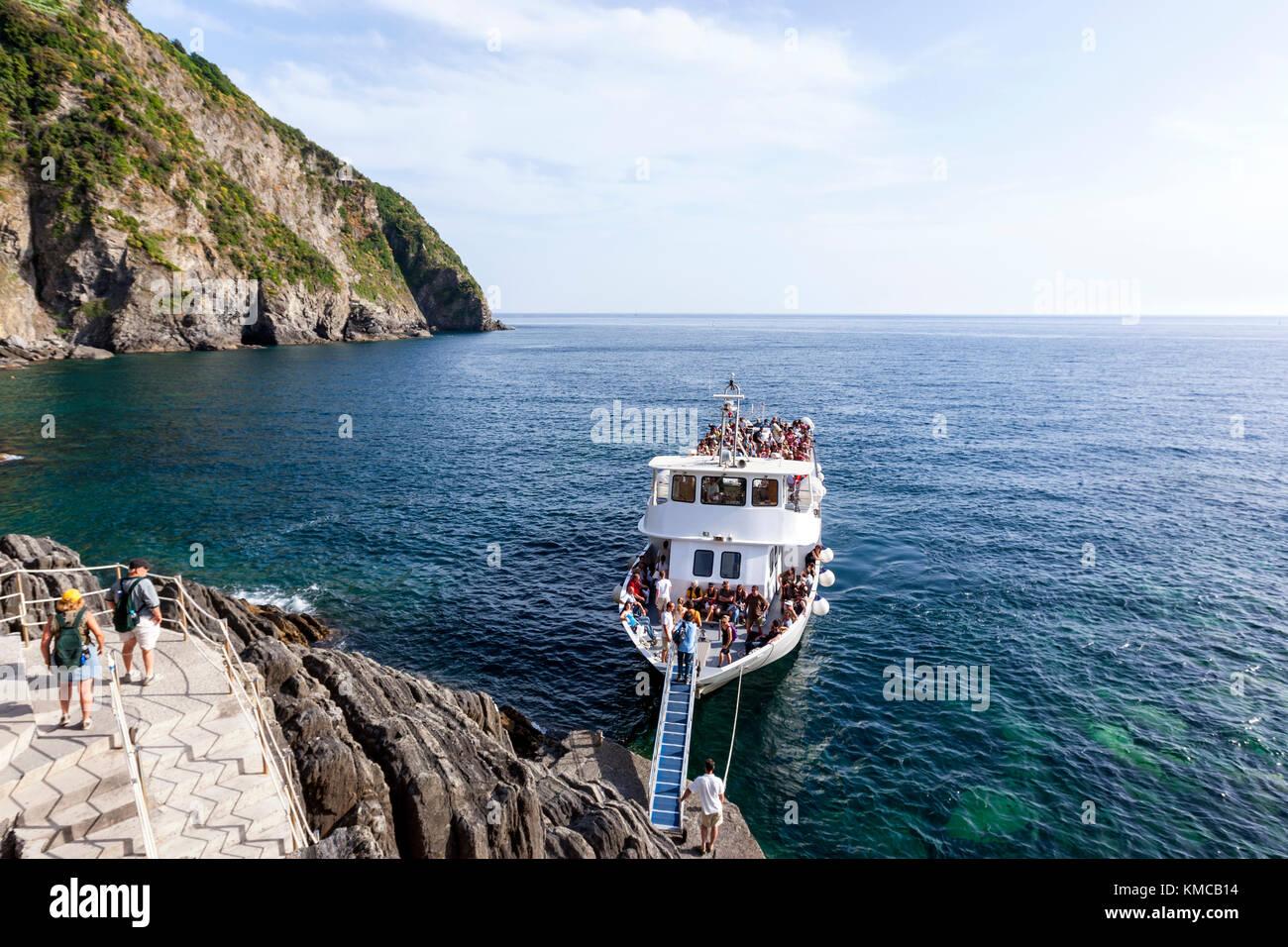 Tourists boat along the Italian Riviera in Riomaggiore, Cinque Terre, province of La Spezia, Liguria region, Italy.Stock Photo