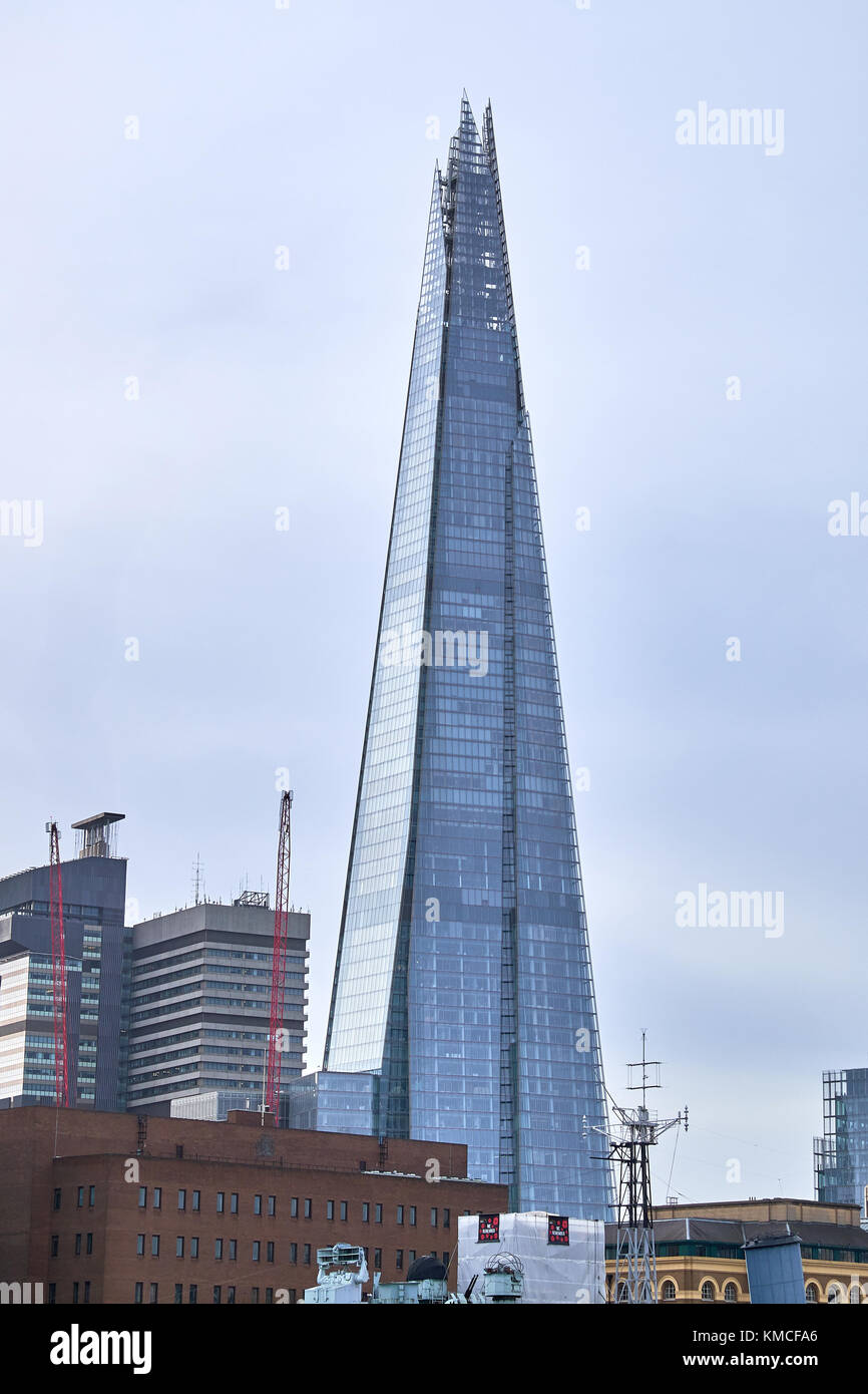 LONDON CITY - DECEMBER 24, 2016: The pointy skyscraper Shard rising towards a gray sky among lower buildings - Stock Image