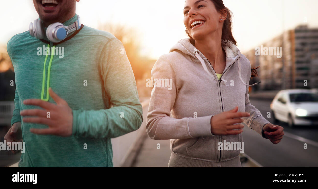 Young fitness couple running in urban area - Stock Image