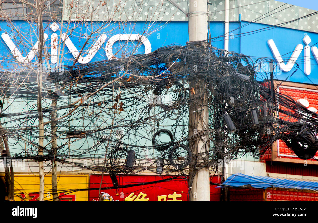 A tangled mess of electric and telephone wires top tall poles through much of central Xian,giving rise to questions - Stock Image