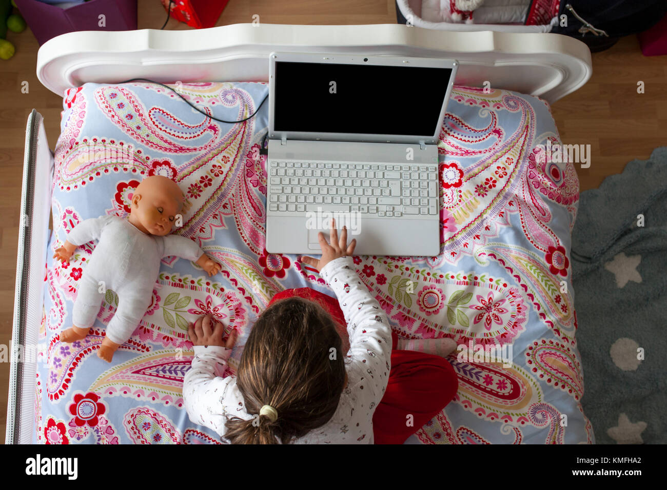 Little Girl Sitting In Bed And Playing Online Games In Her Bedroom