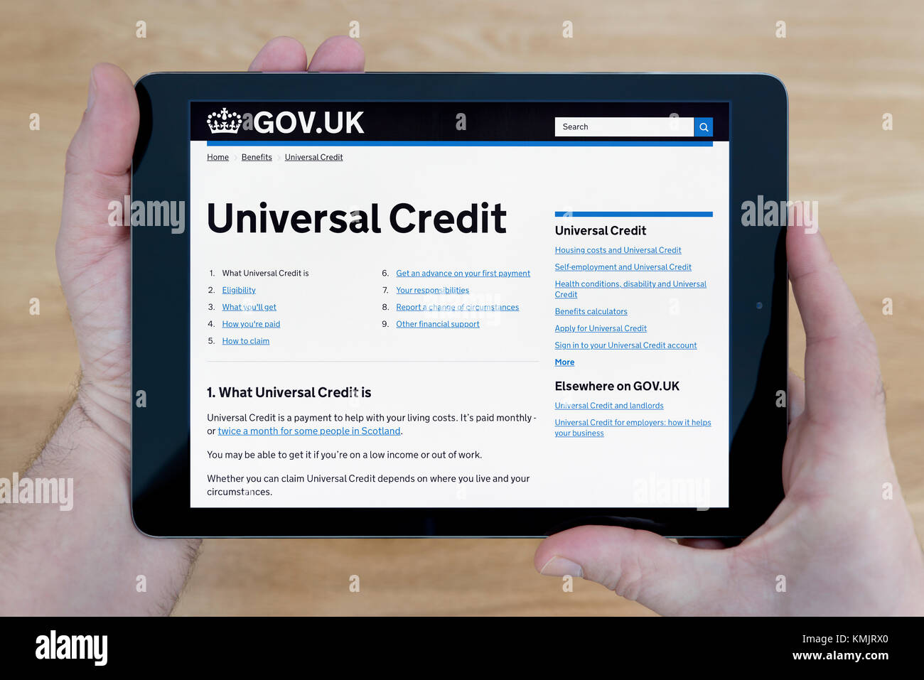 A man looks at the Universal Credit section of the Gov.uk website on an iPad tablet device, shot against a wooden Stock Photo