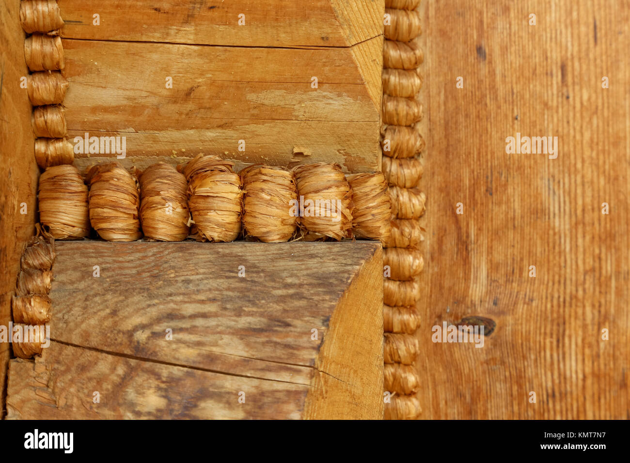 A fragment of the structure of a wooden house shows the joining of wooden logs and their sealing with specially - Stock Image