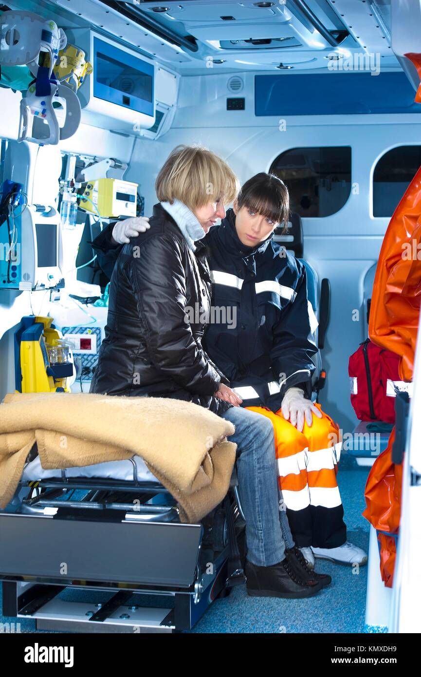 Female Paramedic Assistting Injured Woman - Stock Image