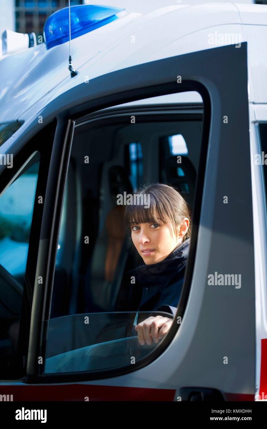 Female Paramedic Driving Ambulance - Stock Image