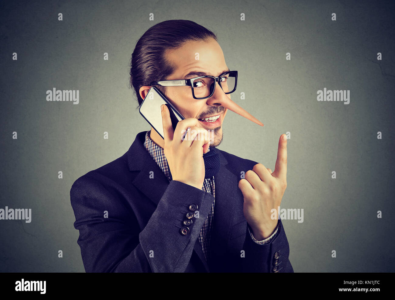 Sly liar business man with long nose talking on mobile phone isolated on gray wall background. - Stock Image