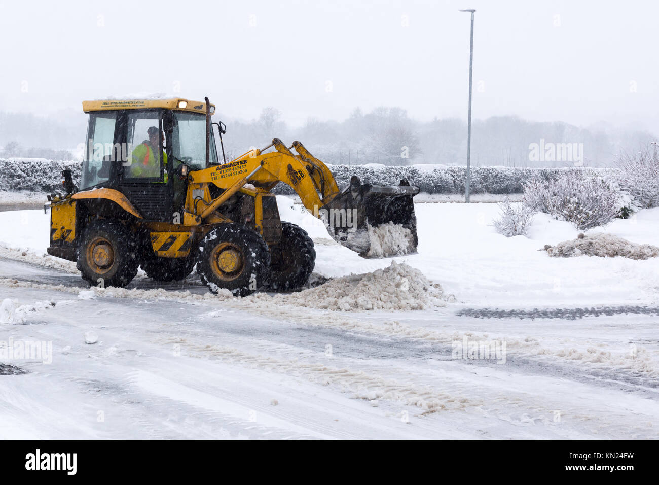 Local contractor attempting to clear the heavy snow fall on a housing estate in Chirk North East Wales Stock Photo