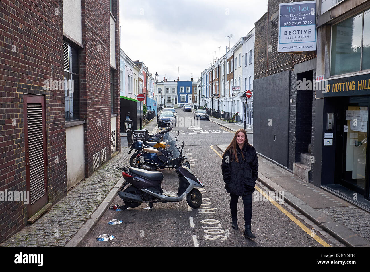Girl walking in an alley with mopeds parked at the curb - Stock Image