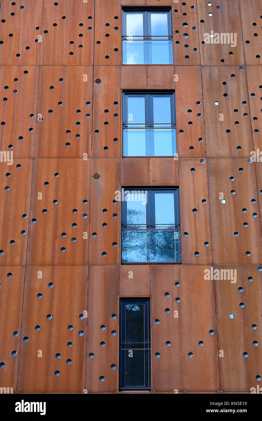 Windows with french balcony in building facade with rusty metal plates with round holes - Stock Image