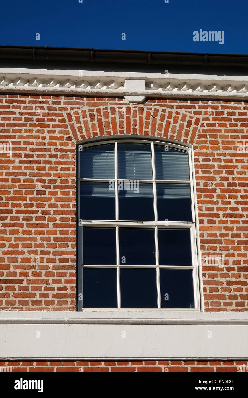 Modernised arched metal window with aluminum blinds in a red brick facade - Stock Image