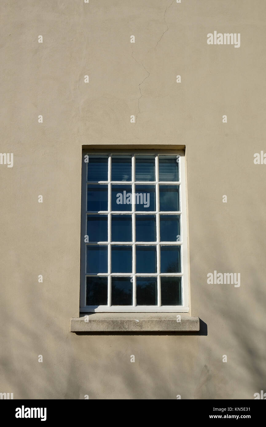 Big square window with small glazing pattern made of many mullions in a plastered building facade - Stock Image