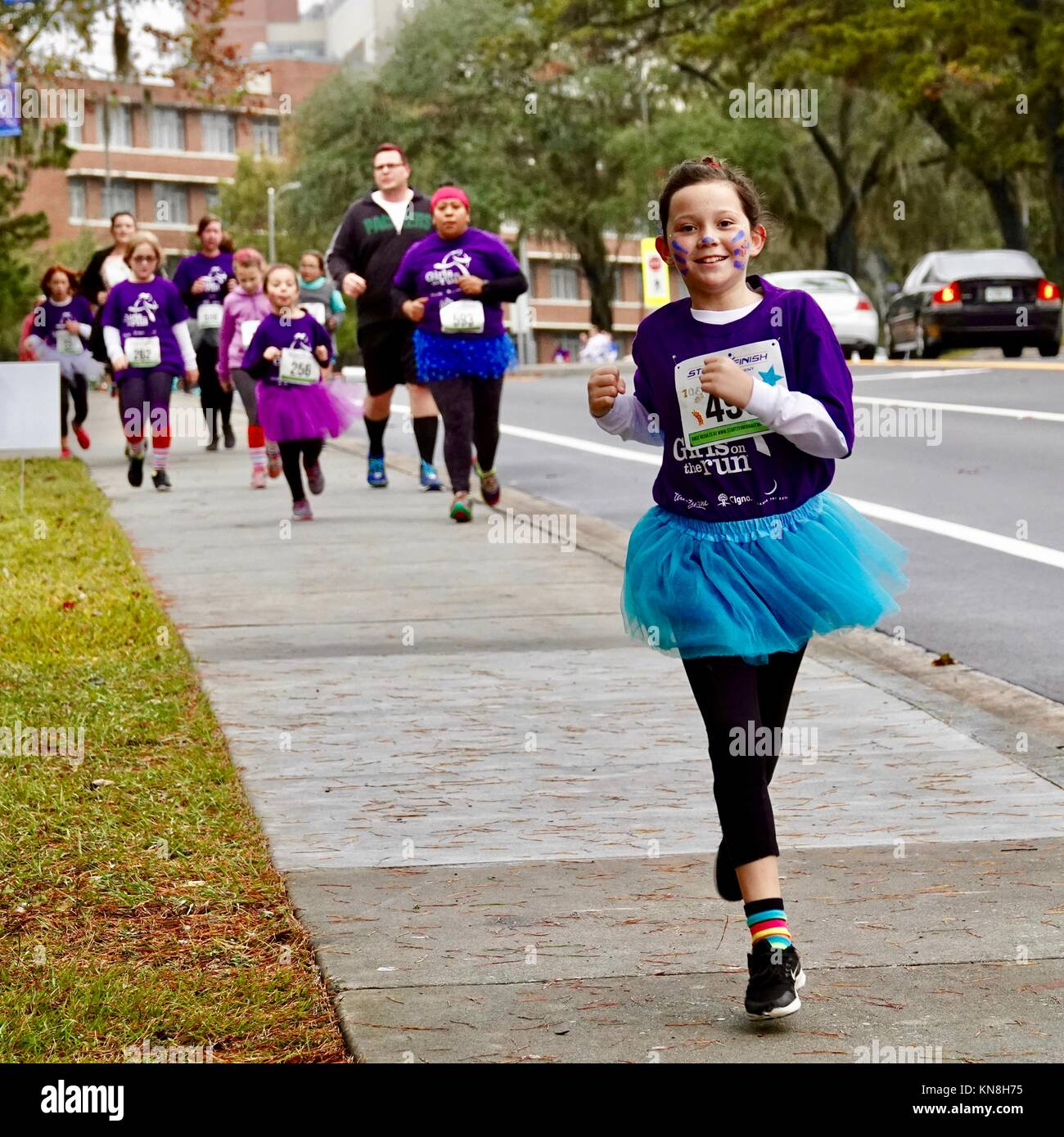 young-girl-racing-ahead-of-a-group-of-ru