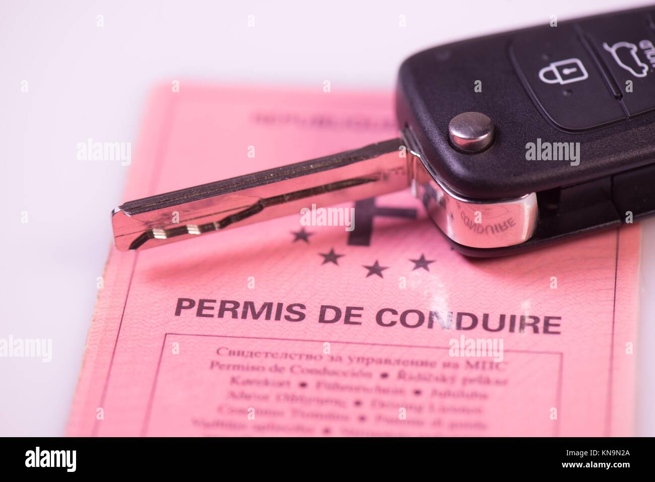 Car keys and drivers license on white background, France. - Stock Image