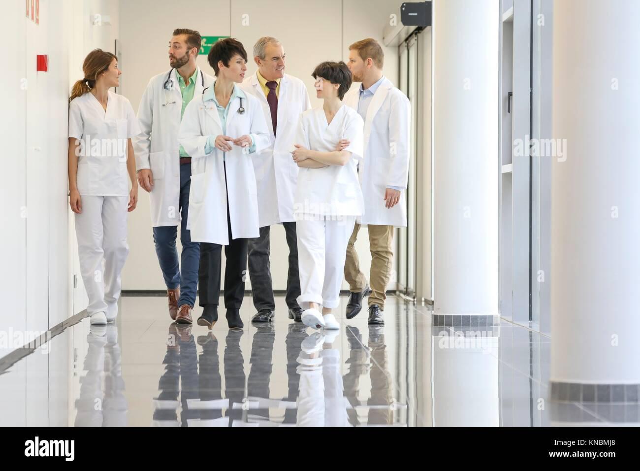 Doctors and nurses walking in corridor, Hospital - Stock Image