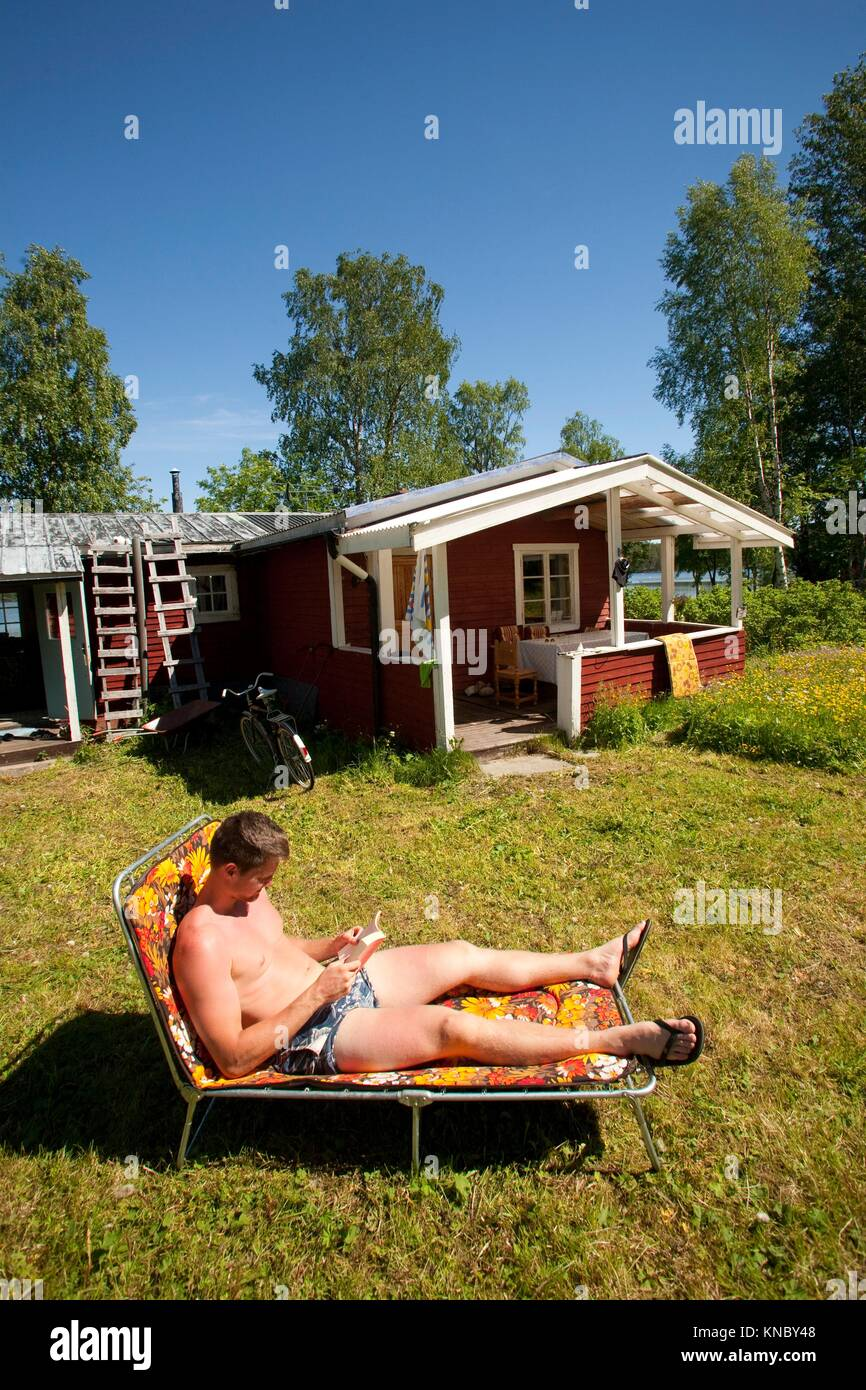 Man reading in the sun, countryside of northern Sweden. - Stock Image