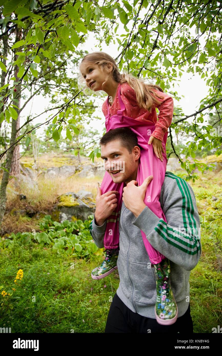 Girl sitting on man's shoulders, Swedish archipelago. - Stock Image